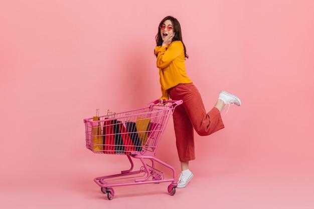 Удивленная девушка в розовых брюках позирует с тележкой, полной разноцветных пакетов с новой одеждой.