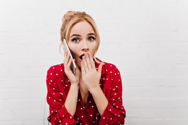 電話で話している赤いナイトウェアの驚いた女の子。驚きを表現するスマートフォンとヨーロッパの女性モデルのクローズアップ屋内ポートレート。