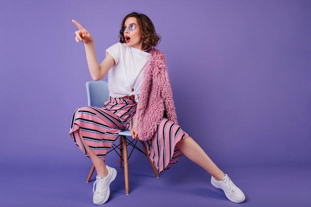 椅子に座って目をそらしている流行のズボンで驚いた女の子。紫色の壁の写真撮影中に驚きを表現する白いスニーカーでスタイリッシュなブルネットの女性の屋内の肖像画。