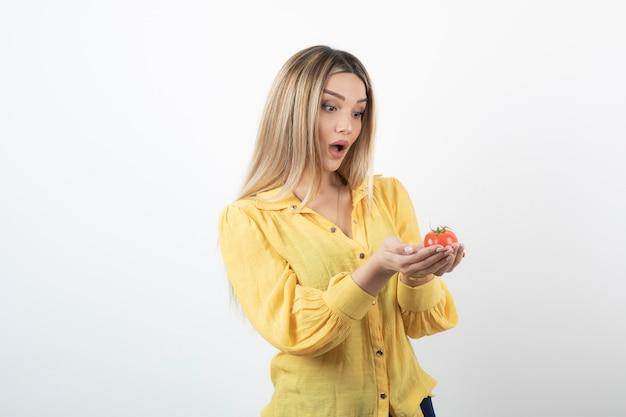 Ragazza sorpresa guardando pomodoro rosso su bianco.