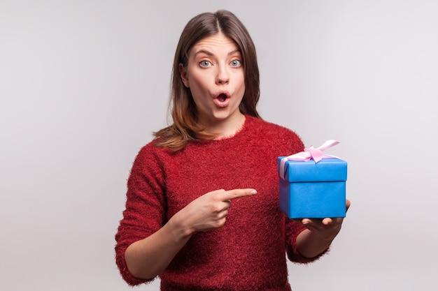 Удивленная девушка указывает на украшенную упакованную подарочную коробку и смотрит в камеру с удивленным выражением лица