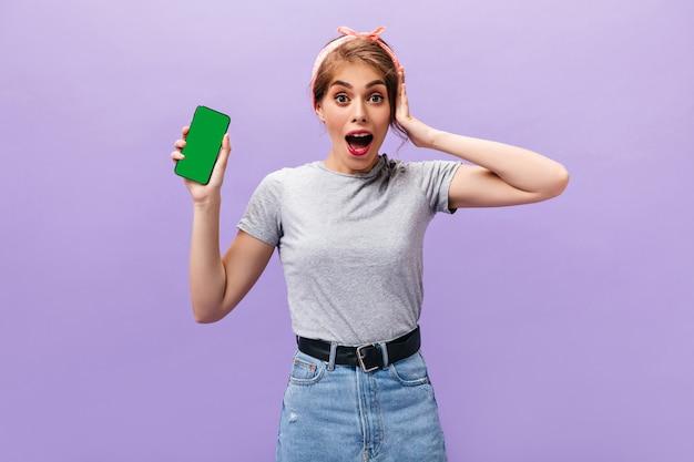 驚いた女の子は紫色の背景に携帯電話でポーズします。ベルト付きの軽いtシャツとスカートでショックを受けた現代の女性はスマートフォンを保持します。