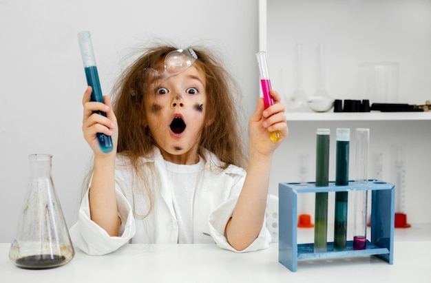 Surprised girl scientist in the laboratory with test tubes and failed experiment