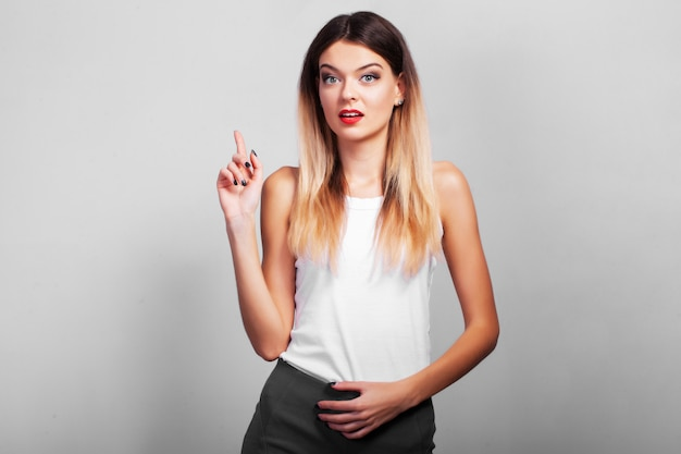 Удивленная девушка показывает ваш продукт рукой