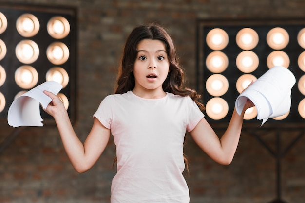 Surprised girl standing in front of stage light holding scripts