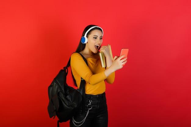 ヘッドフォンを身に着けているバックパックと黄色のメモ帳で驚いた女子学生は、赤い表面で隔離された携帯電話を保持しています。