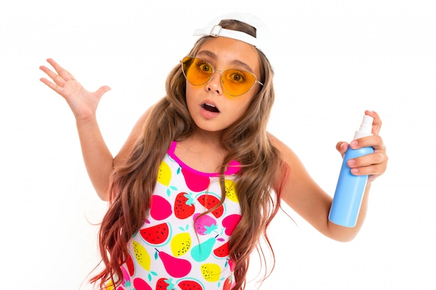 Surprised girl in a summer look holds a bottle of sunscreen on a white wall