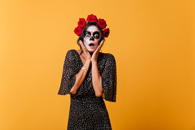 Surprised girl took hold of her face and looked in shock. lady in black outfit, rose crown and skeleton mask posing on orange wall.