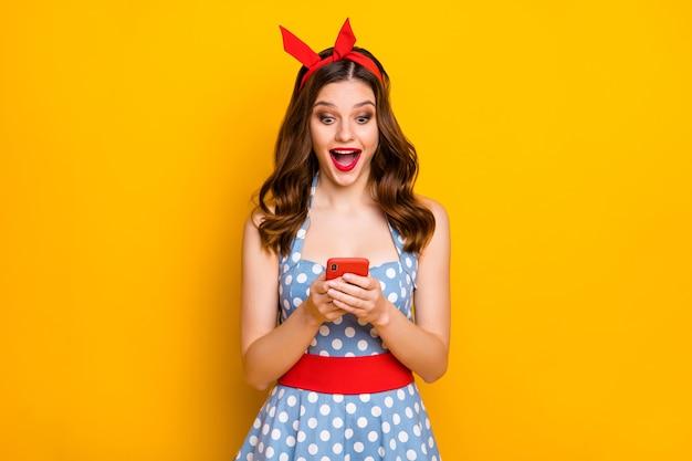 놀란 된 소녀 노란색 배경에 스마트 폰 블로깅 비명을 사용