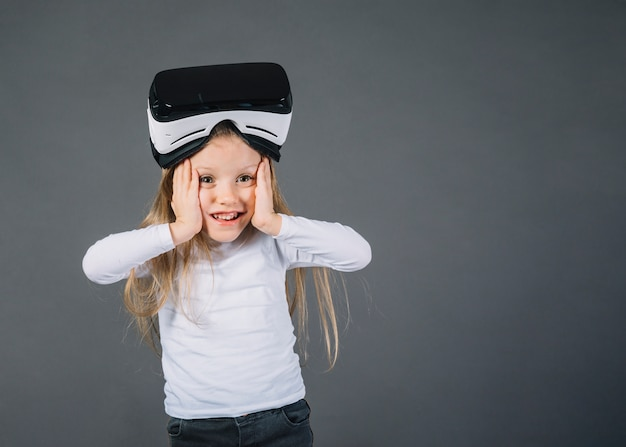 Surprised girl wearing virtual reality glasses on her head touching her cheeks against gray background