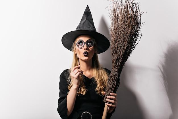 Ragazza sorpresa con labbra nere in posa al carnevale di halloween. splendida signora dai capelli lunghi in costume da strega in piedi sul muro bianco.