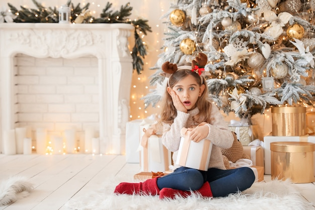 Surprised girl with christmas gift at home