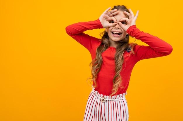 赤いブラウスと縞模様のズボンの巻き毛を持つ驚いた女の子は、コピースペースのあるオレンジ色の背景の手のひらをのぞきます。