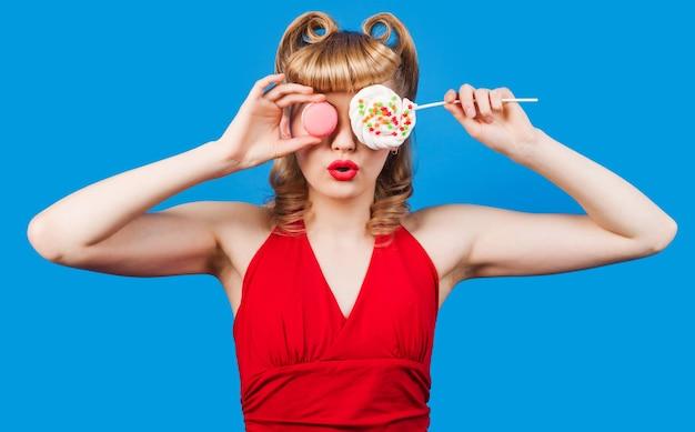 ロリポップとマカロンで驚いた女の子。甘い食べ物、ダイエット、ダイエットの概念。