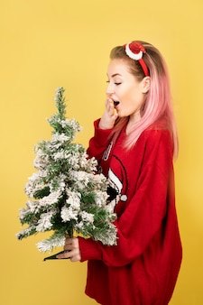 Surprised girl with new year tree