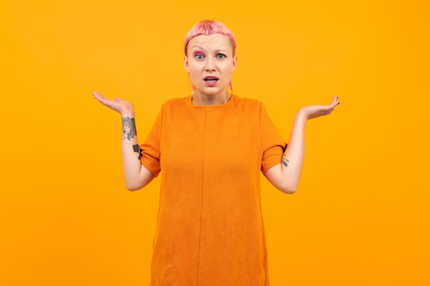Удивленная девушка с розовыми волосами и пронзенным лицом, одетая в свободное оранжевое платье, развела руки по сторонам на желтом