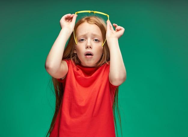 Удивленная девушка с рыжими волосами держит в руках очки эмоции зеленый фон школа
