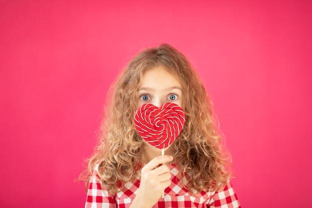 Удивленная девушка с красным леденцом в форме сердца на розовом фоне концепции дня святого валентина