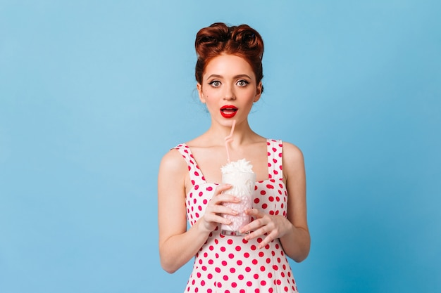 Surprised girl with red lips drinking milkshake. studio shot of emotional young lady in polka-dot dress standing on blue space.