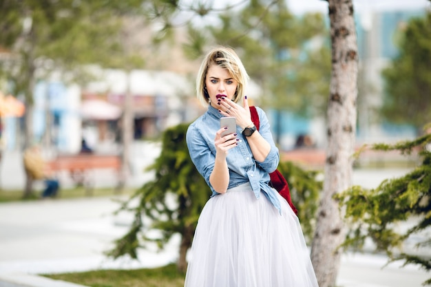 A surprised girl with short blond hair and bright pink lips looking at a smartphone