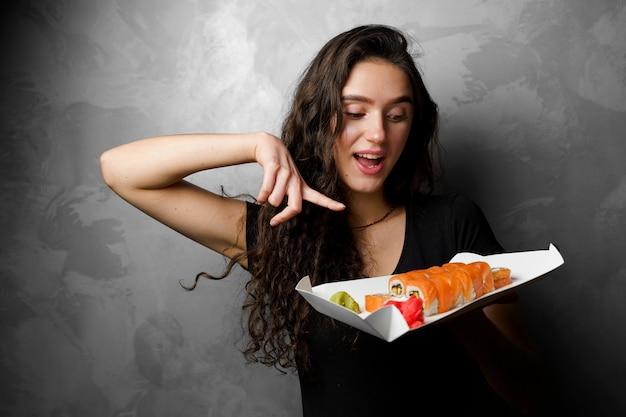 스시 세트와 놀된 소녀 필라델피아 종이 상자에 롤 회색 배경에 들고 행복 한 소녀입니다. 음식 배달.