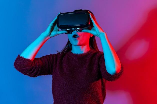 게임 시뮬레이터를 재생하는 가상 현실 안경을 쓴 놀란 소녀