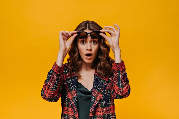 Surprised girl with wavy hair in striped jacket takes off glasses on isolated wall