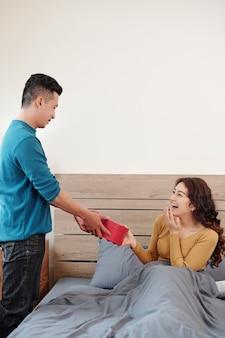 발렌타인 데이 아침에 남자 친구로부터 큰 하트 모양의 상자를 받고 놀란 여자 친구