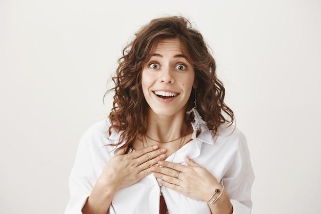 驚きのうれしい女性は良いニュースを受け取り、感謝し、満足しているように見える
