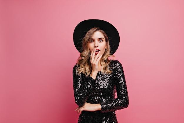 놀란 된 매력적인 여자. 분홍색 벽에 서있는 검은 모자에 열정적 인 예쁜 여자.