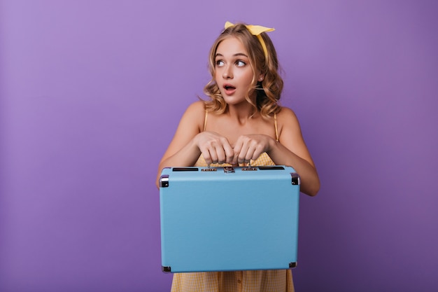 Bella donna sorpresa che posa con i bagagli. ritratto dell'interno della ragazza bionda curiosa che tiene valigia blu sulla porpora.