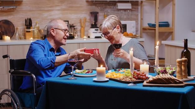 축제 저녁 식사 중에 주는 할아버지의 선물을 보고 놀란 할머니. 집에서 아내와 식사를 하고 식사를 즐기고 그들의 안식일을 축하하는 고정된 마비된 노인 남편