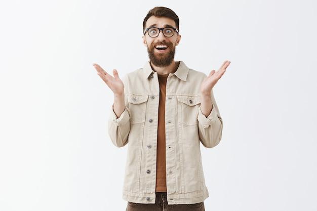 Uomo barbuto sorpreso e grato in bicchieri in posa contro il muro bianco