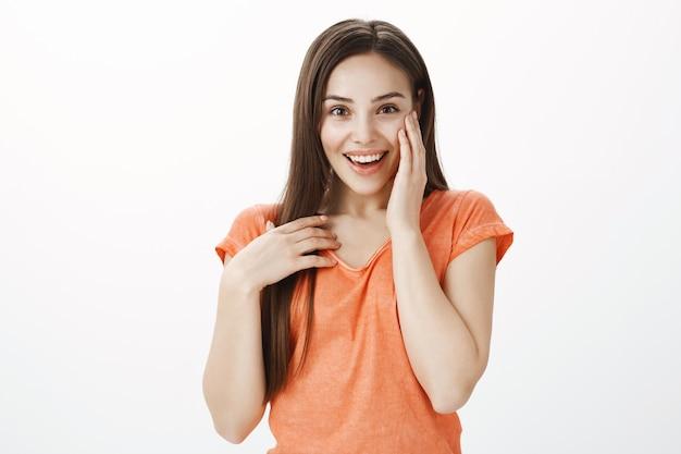 Ragazza bruna carina sorpresa e grata che tiene le mani sul cuore, che sembra felice o grato