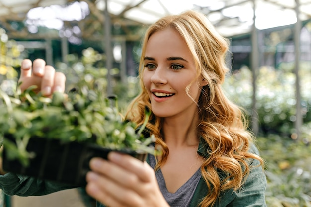 Surprised green-eyed lady looks at plant in amazement. portrait of cute long-haired european model who loves botany.