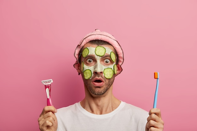 Surprised guy applies clay mask and slices of cucumbers to cleanse skin, holds razor for shaving and brushing teeth, wears rosy bath cap