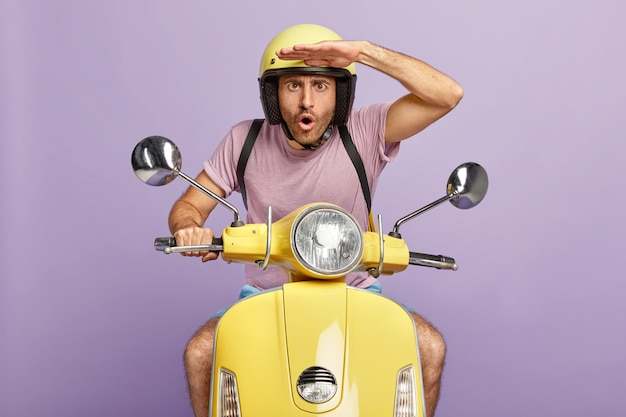 Surprised guy drives fast motorbike, focused into distance, keeps hands on forehead, wears yellow helmet and t shirt, delivers order to customer, isolated on purple wall. shocked motorcyclist