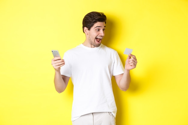 Удивленный парень, держащий смартфон и кредитную карту, интернет-магазины в черную пятницу, стоя на желтом фоне.
