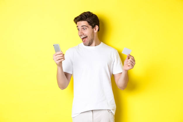 Surprised guy holding smartphone and credit card, online shopping on black friday, standing over yellow background.