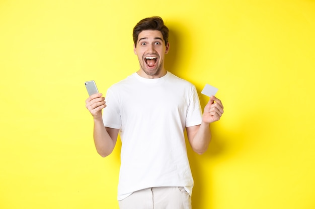 Surprised guy holding smartphone and credit card, online shopping on black friday, standing over yellow background. Free Photo
