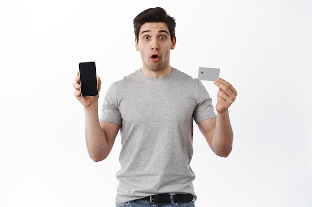 Surprised guy shows empty cellphone screen and plastic credit card, gasping and say wow, impressed with online store, makes order, stands against white wall