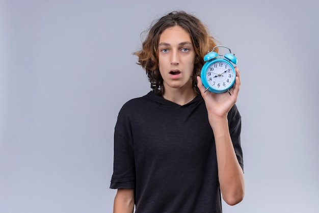Surprised guy with long hair in black t-shirt holding a alarm clock on white background