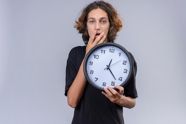 壁掛け時計を保持している黒のtシャツに長い髪を持つ驚いた男と白い背景の上の手で口を覆った