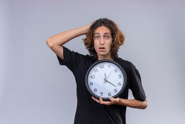 壁掛け時計を保持している黒のtシャツに長い髪を持つ驚いた男と白い背景の上に頭を掴んだ