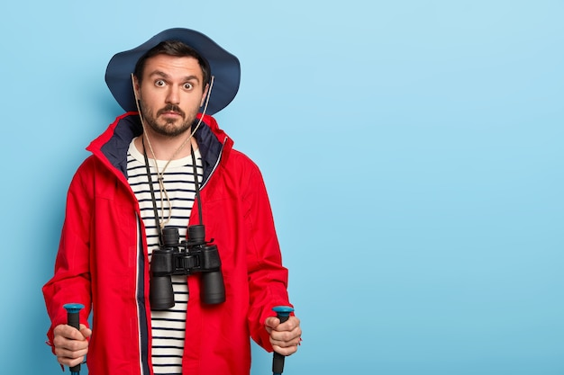 Surprised guy with mustache wears hat and red jacket, carries walking sticks, uses binoculars for exploration place, breathes fresh air, poses over blue wall