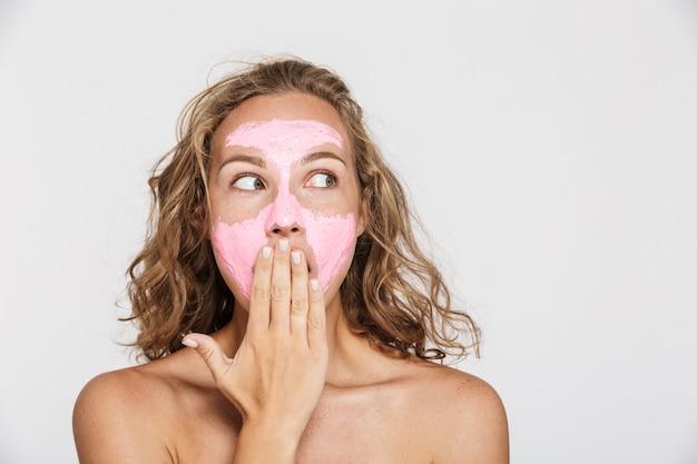 フェイスマスクで驚いた半裸の女性が脇を見て、白い壁に隔離された彼女の口を覆っている