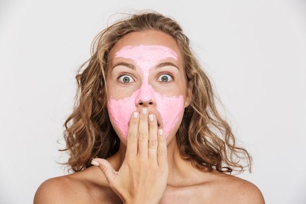 カメラを見て、白い壁に隔離された彼女の口を覆っているフェイスマスクで驚いた半裸の女性