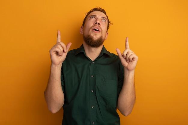 놀란 잘 생긴 금발의 남자가 외모와 오렌지 벽에 고립 된 두 손으로 포인트