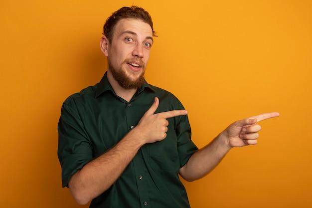 오렌지 벽에 고립 된 두 손으로 측면에서 놀된 잘 생긴 금발 남자 포인트