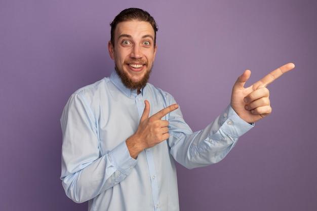 L'uomo biondo bello sorpreso indica a lato con due mani isolate sulla parete viola